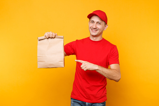Man in red cap, t-shirt giving fast food order isolated on yellow background. Male employee courier hold empty paper packet with food. Products delivery from shop or restaurant to home. Copy space.