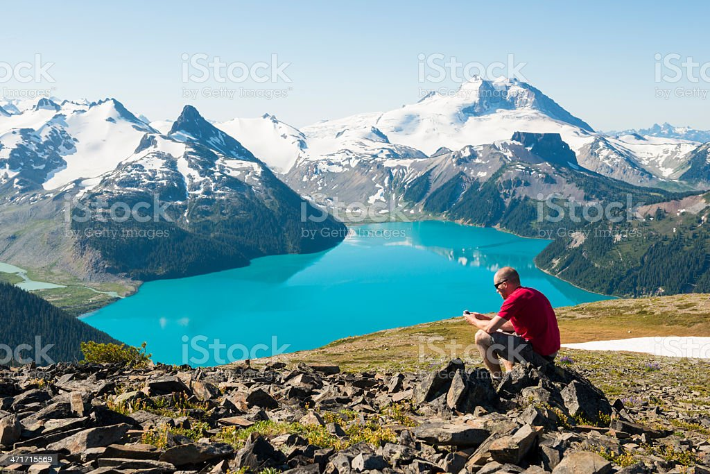 Man in red on a rock using cell phone over the mountains stock photo