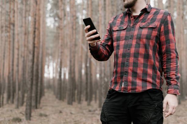 25fd7dd668 Hombre en rojo camisa a cuadros y pantalón militar negro tiene un teléfono  inteligente en su