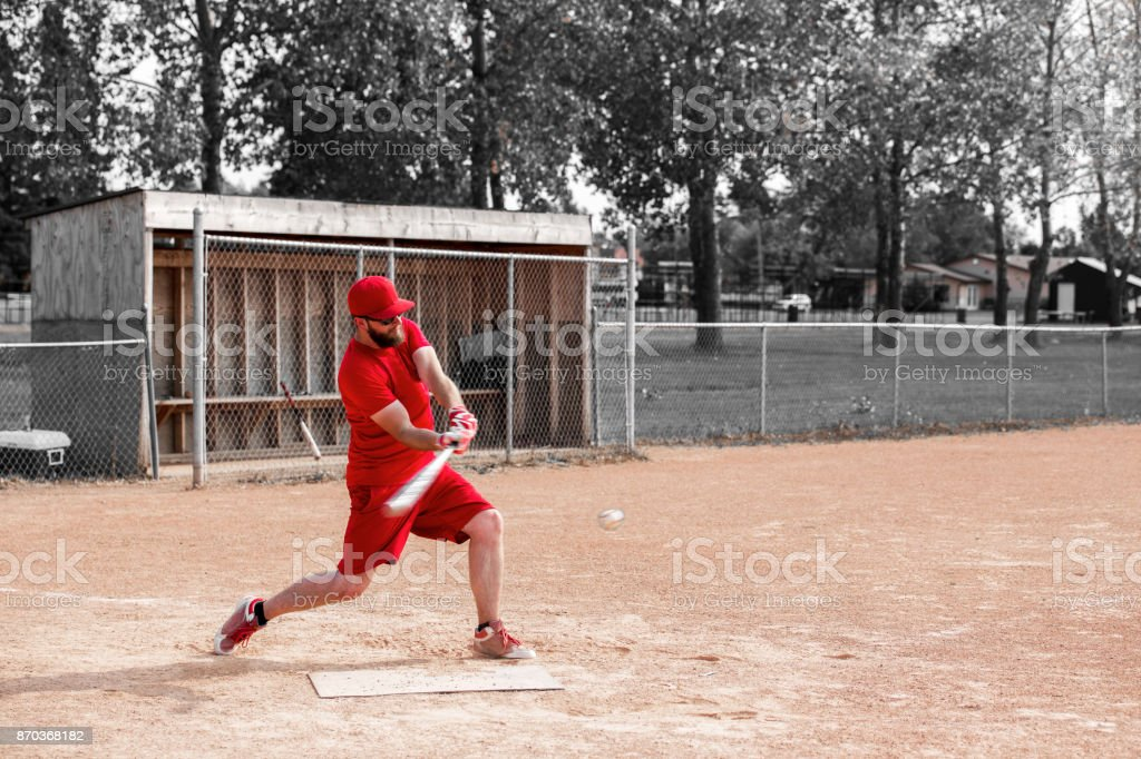 Man in red playing baseball stock photo