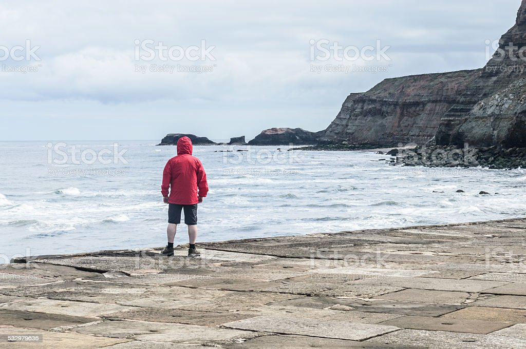 Man in red rain jacket cagoule on Whitby Harbour stock photo