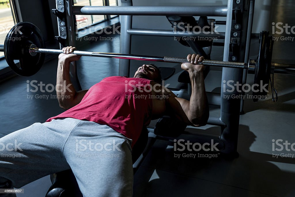 Man in red shirt lifts weights using a bench press stock photo