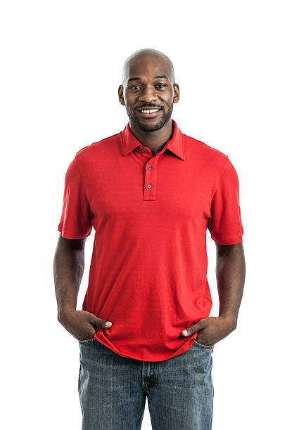 Man in red shirt smiling on white background  Portrait of a late 20s handsome black casual businessman with hands in pockets isolated on a white background red shirt stock pictures, royalty-free photos & images