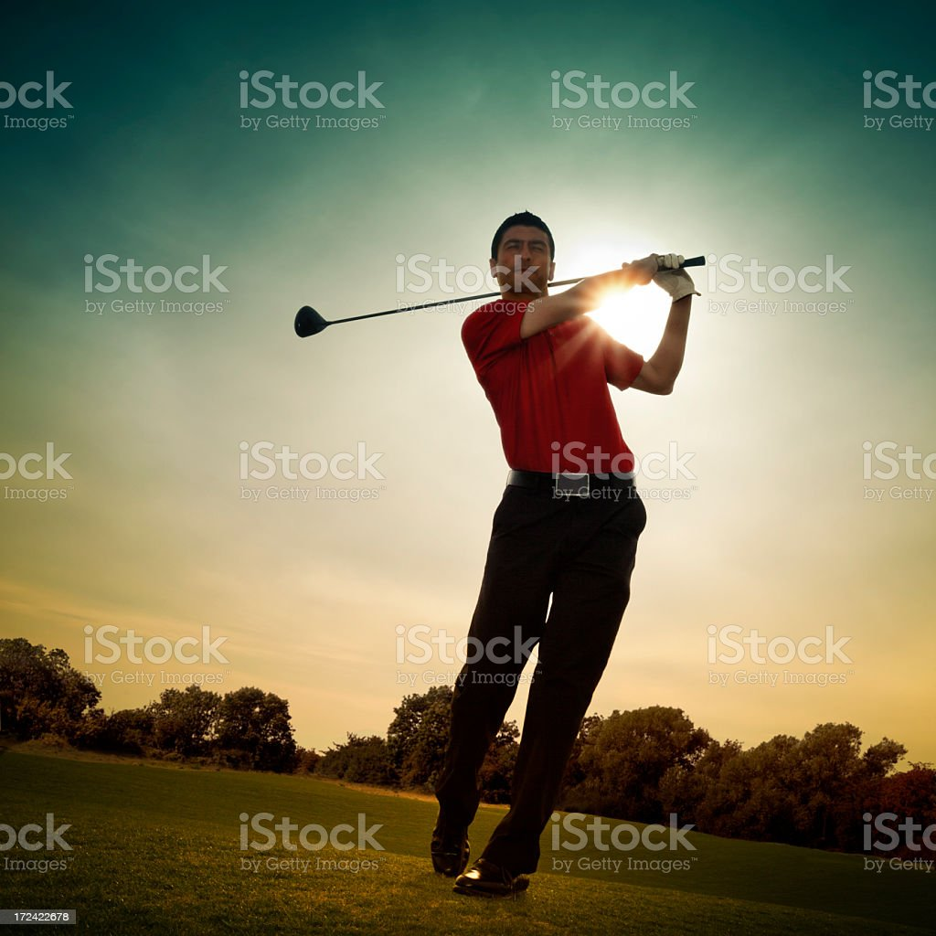 Man in red shirt swinging golf club by sunlight royalty-free stock photo