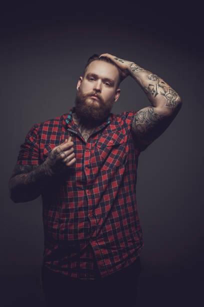 hombre de camiseta roja y tatuajes. - hombres grandes musculosos fotografías e imágenes de stock