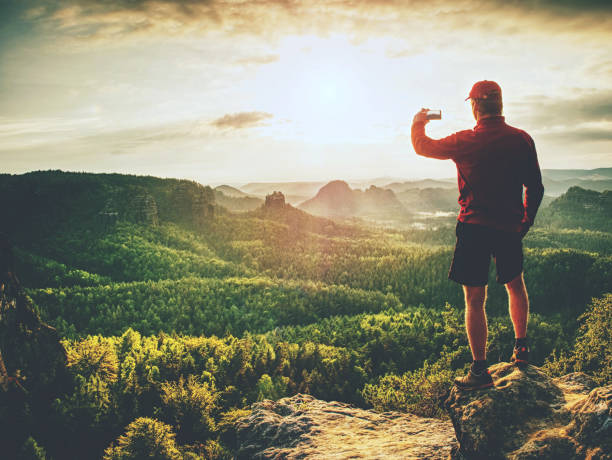 Man in red t-shirt and shorts takes photos with smart phone on peak stock photo