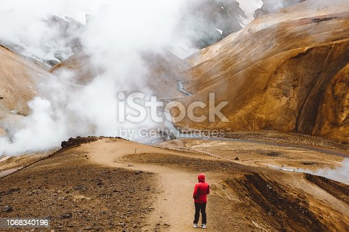 Man in red jacket and eyeglasses exploring the unbelievable geothermal geyser mountain area in Icelandic Highlands