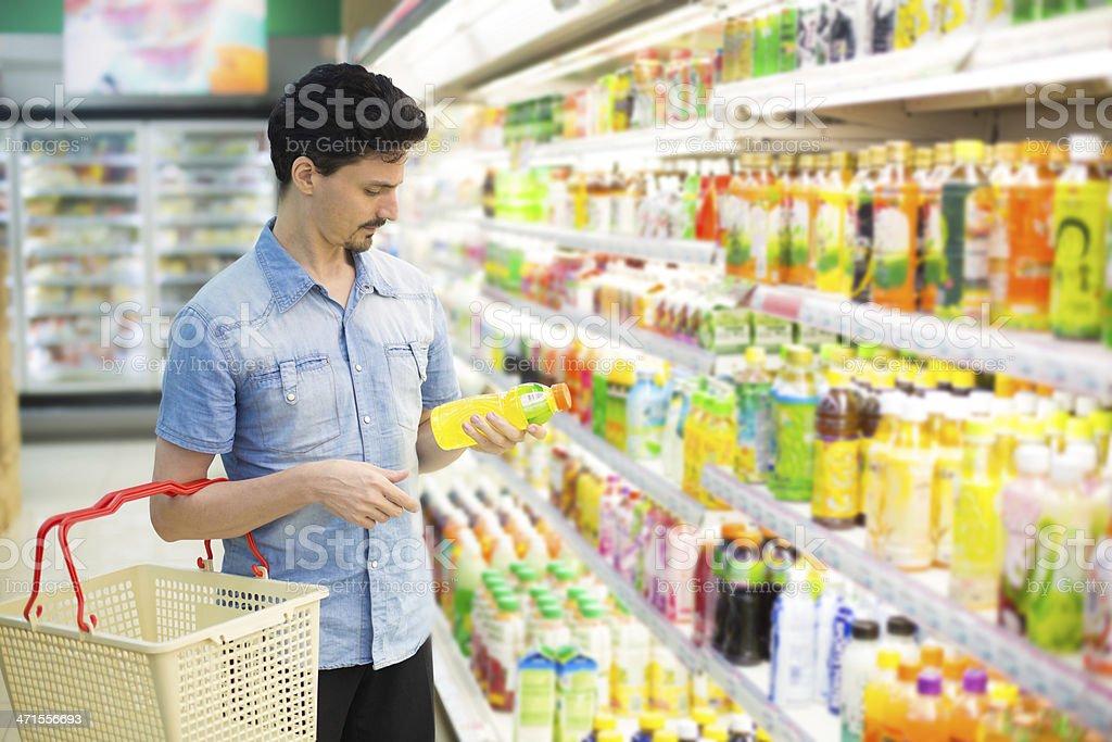 Hombre en supermercado adquirir una botella de jugo foto de stock libre de derechos
