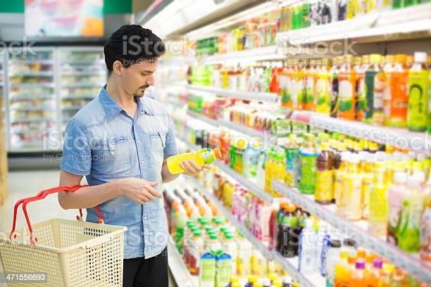 Hombre En Supermercado Adquirir Una Botella De Jugo Foto de stock y más banco de imágenes de Adulto