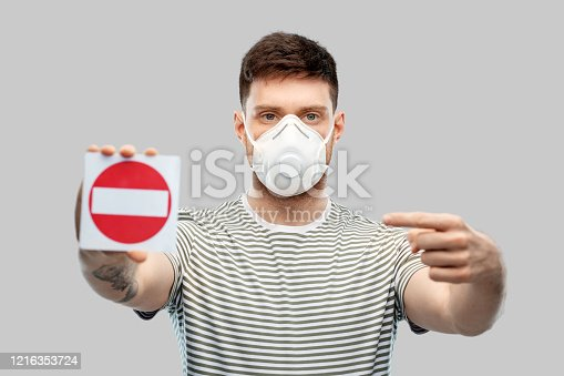 health protection, safety and pandemic concept - young man in protective mask or respirator with valve showing stop sign over grey background