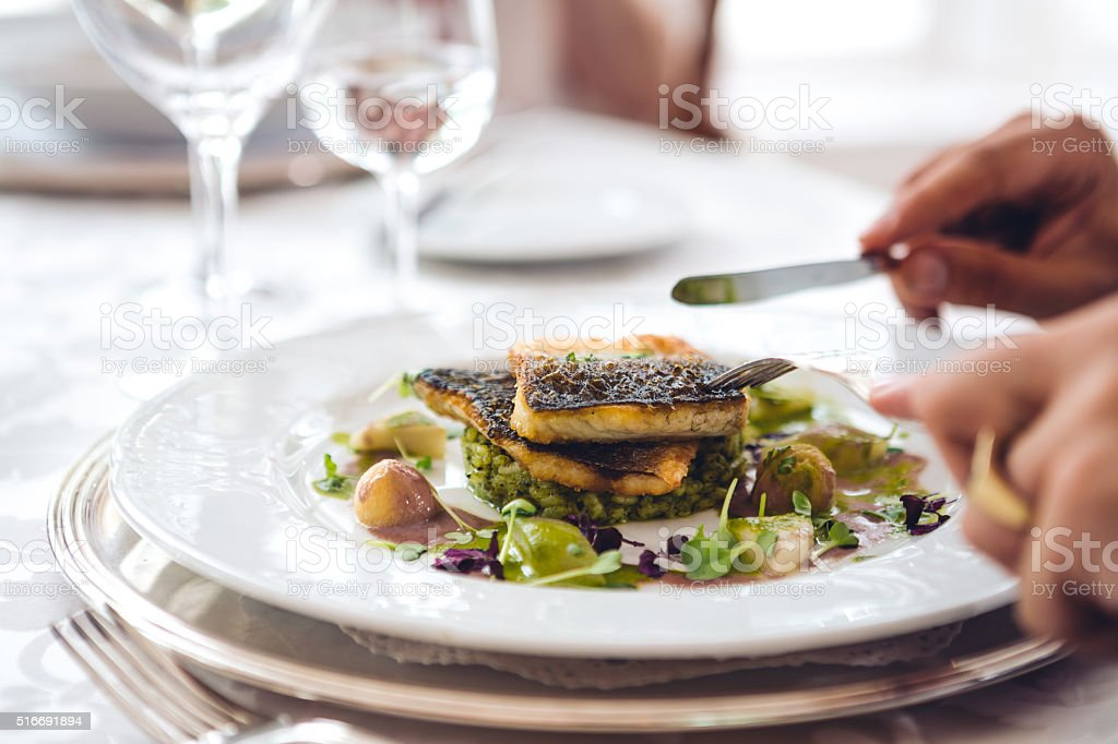Man In Restaurant Eating Fish stock photo