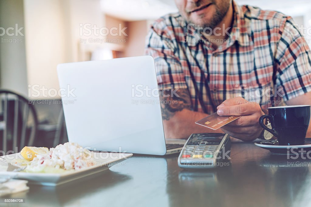 Man in restaurant making contactless payment stock photo