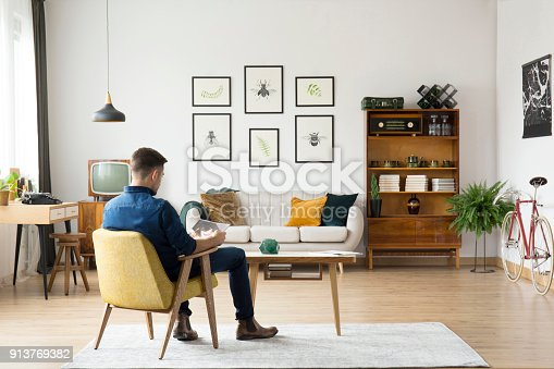 Man sitting on yellow chair at wooden table in retro living room with sideboard and gallery above settee