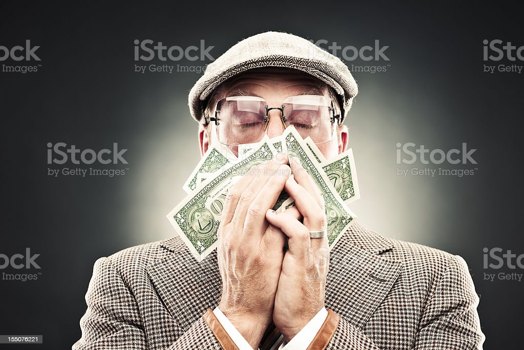 Man in retro suit smelling money royalty-free stock photo