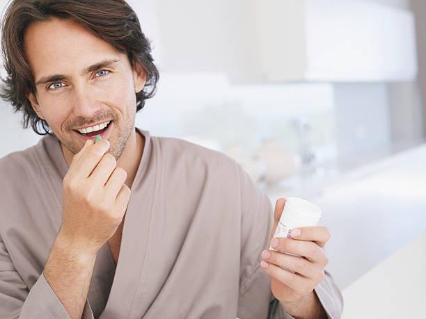 Mann in Bademantel hält Vitamintablette – Foto
