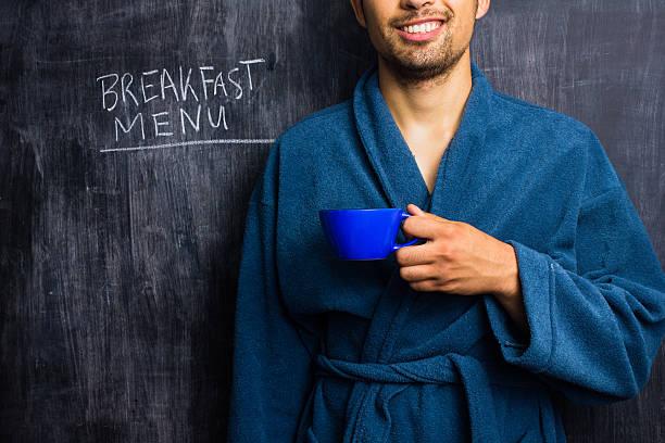 Mann in Bademantel neben Frühstück-Menü auf Tafel – Foto