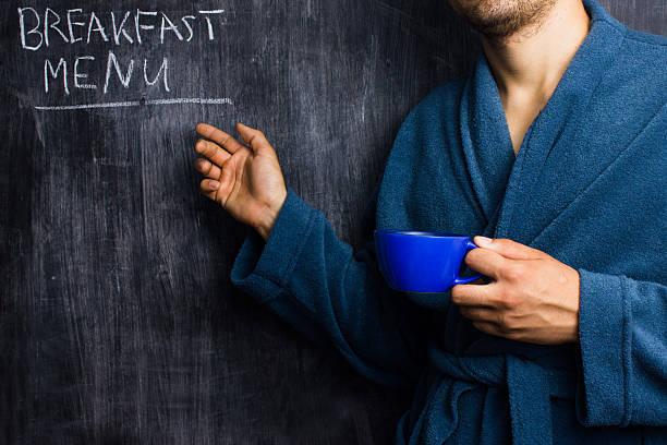 Mann in Bademantel zeigt beim Frühstück-Menü auf Tafel – Foto