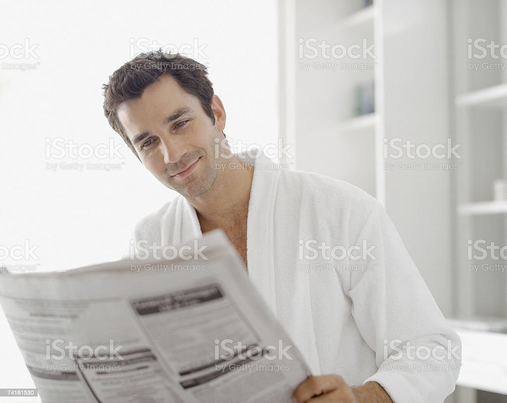 Man in robe reading newspaper royalty-free stock photo