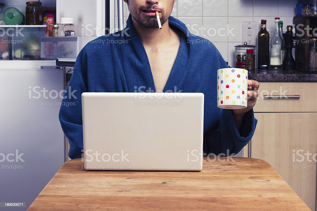 Man in robe working from home and smoking royalty-free stock photo