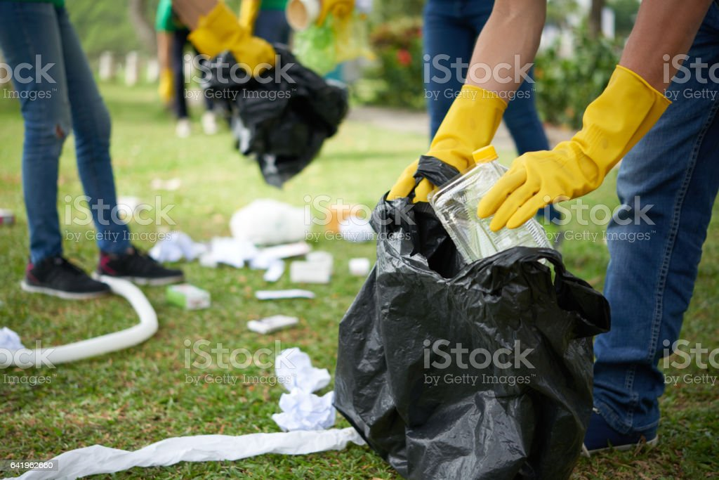 Man in rubber gloves collecting rubbish stock photo