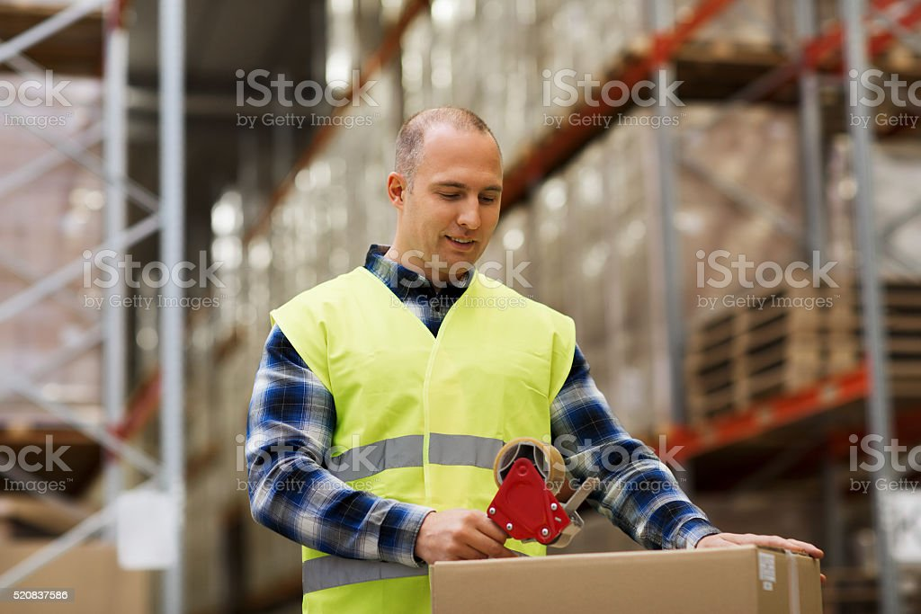 man in safety vest packing box at warehouse stock photo