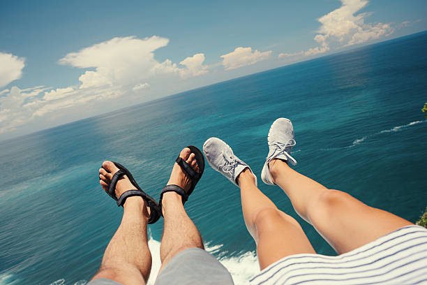 man in sandals and woman above the ocean - woman leg beach pov stock photos and pictures