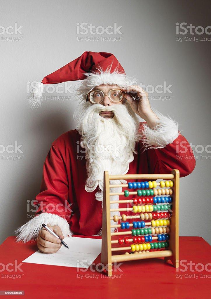 Man in Santa Claus suit using abacus stock photo