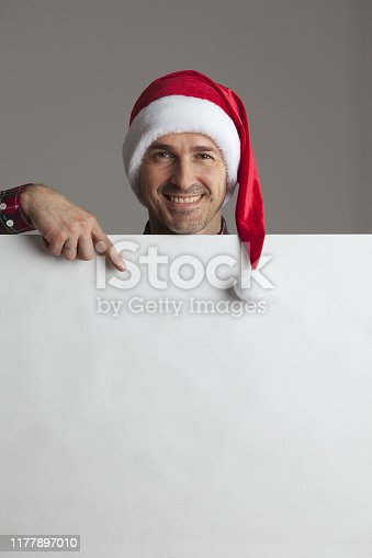 Happy man in Santa hat holding blank banner with copy space