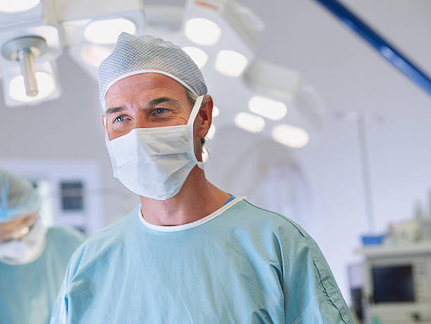 Man in scrubs in operating room stock photo