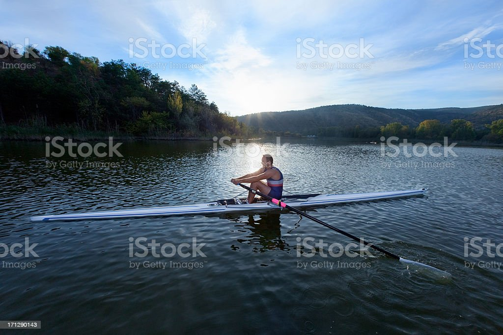 Man in sculling boat rowing across a beautiful blue lake stock photo