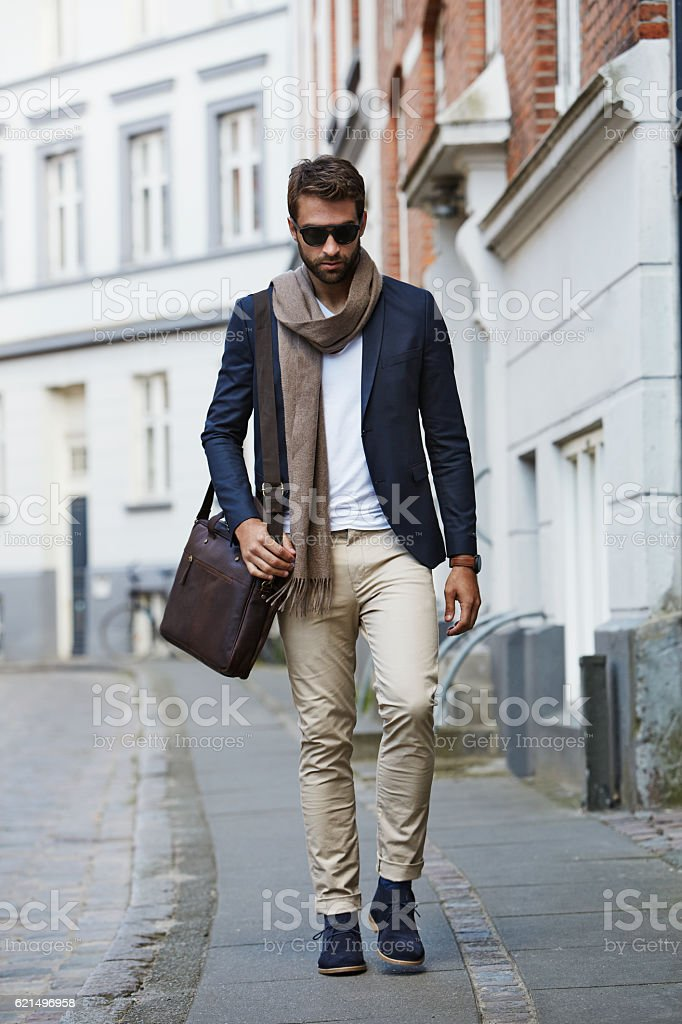 Man in shades and scarf walking through city foto stock royalty-free