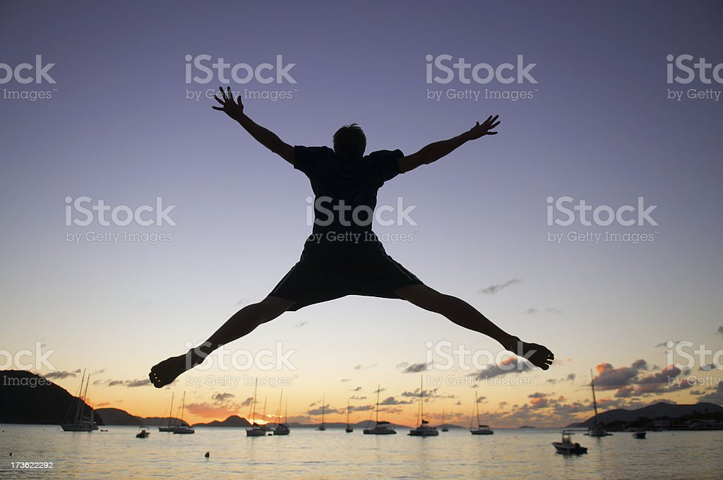 Man in Silhouetted Spreadeagled Sunset Leap stock photo