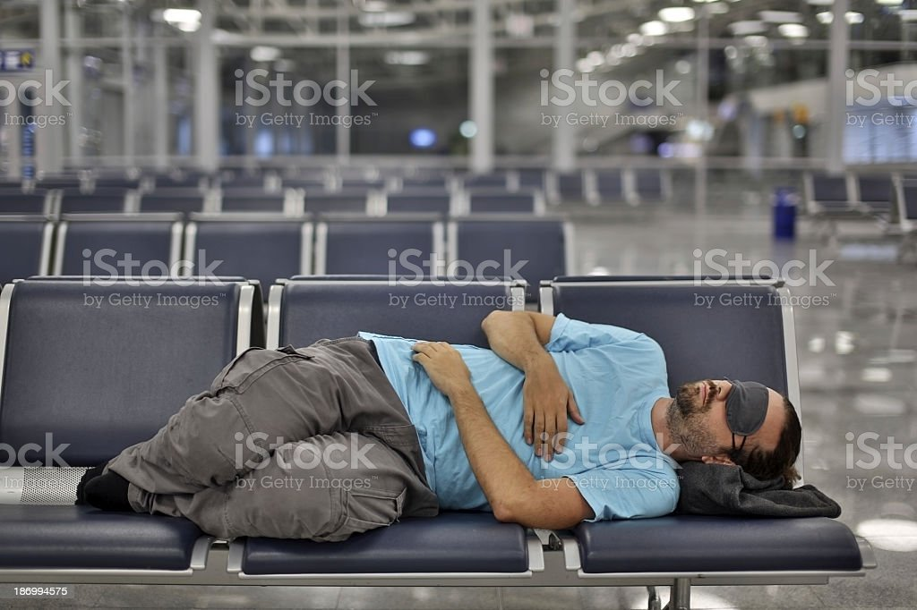 Man in sleeping across chairs in an airport with eye cover stock photo