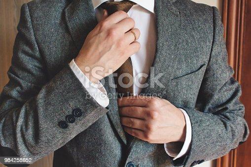 Man in smart suit wearing wedding ring adjusting tie. Elegant tailor-made clothing.