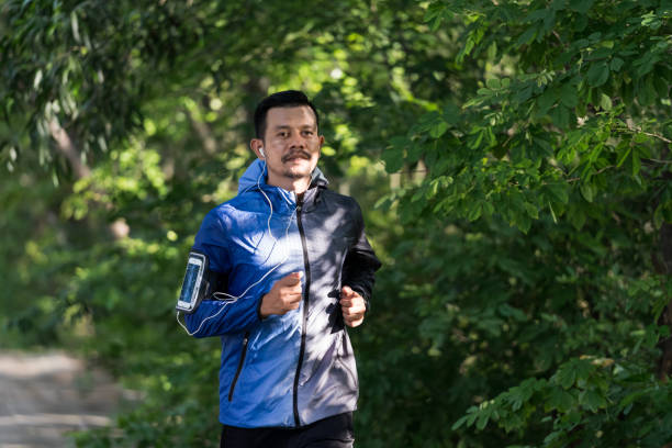 A man in sport hoodie jogging in the city park in the evening after stressful work. stock photo