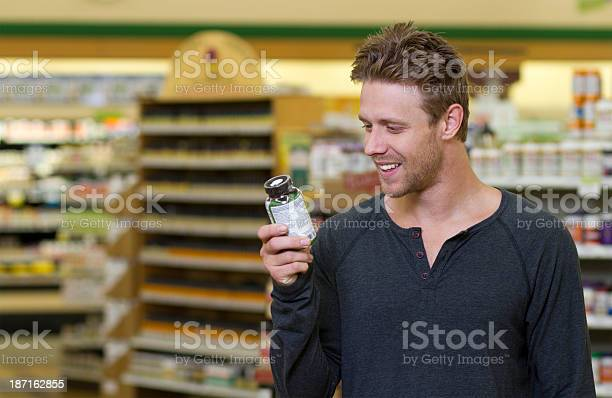 Man In Store Looks At Vitamins Stock Photo - Download Image Now