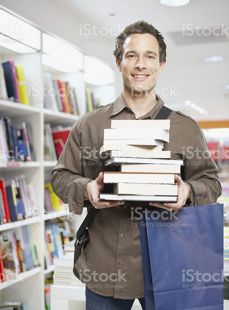 Man in store with stack of books royalty-free stock photo