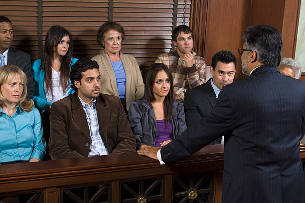 Man in suit addressing jurors in courtroom stock photo