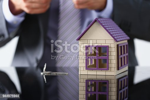 689401592 istock photo Man in suit and tie and silver key and little 944975944