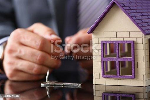 689401592 istock photo Man in suit and tie and silver key and little 944975946