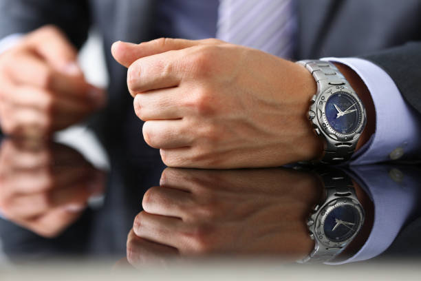 Man in suit and tie check out time at Man in suit and tie check out time at silver wristwatch closeup. Waste minute modern punctual life style start hurry job idea last second clockwork precision concept luxury watch stock pictures, royalty-free photos & images