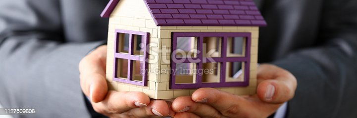 863128060istockphoto Man in suit and tie cover with arms little toy house 1127509606