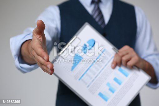 859896852istockphoto Man in suit and tie give hand as hello in office 845882356