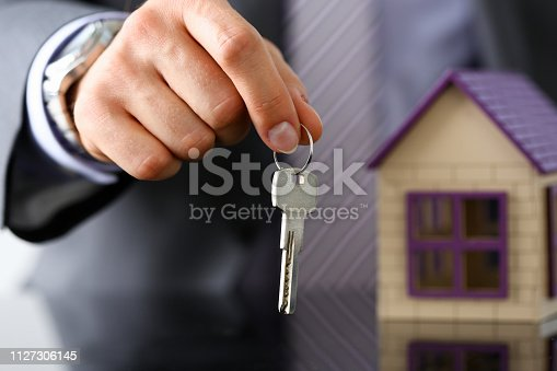 689401592 istock photo Man in suit and tie hold in hand silver key giving 1127306145