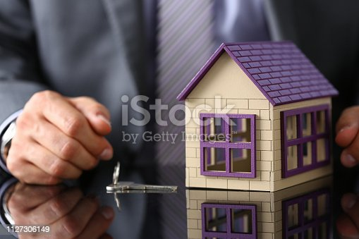 689401592 istock photo Man in suit and tie hold in hand silver key giving 1127306149