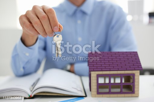 689401592 istock photo Man in suit and tie hold in hand silver key giving 1127340953