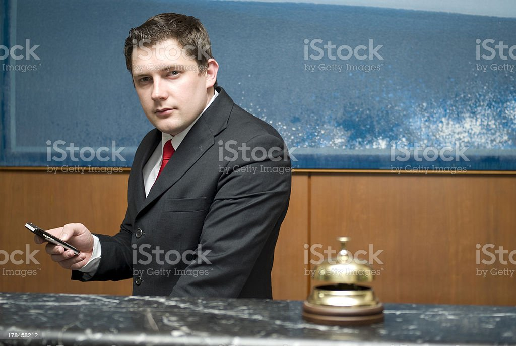 Man in suit behind hotel reception desk with brass bell royalty-free stock photo