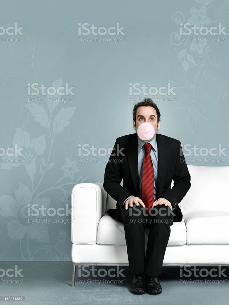 Man in suit blowing chewing gum royalty-free stock photo
