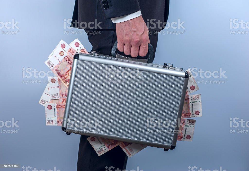 Hombre en traje de metal, maletín de transporte, con billete de rublo ruso - foto de stock