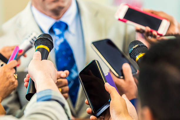 Man in suit confronted by media Older man in a tan suit and blue tie. Journalists use phones and microphones to record what he has to say. surrounding stock pictures, royalty-free photos & images